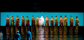 A number of women opera singers dressed as geishas in line on a stage